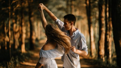 couple dancing in low light in forested area