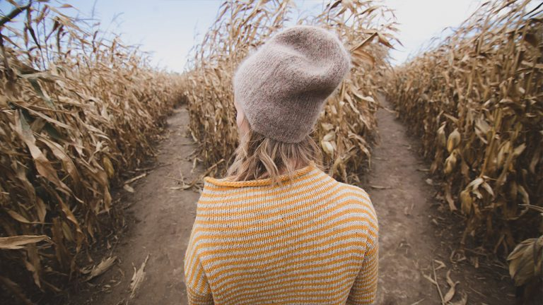 girl stands before two paths in cornfield